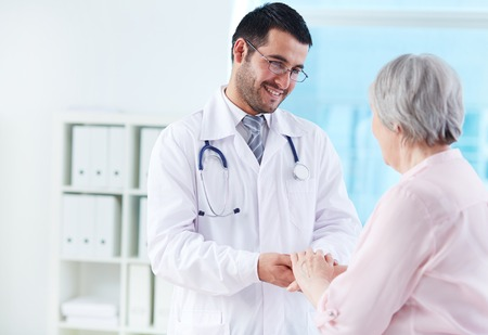 Confident doctor looking at his senior patient while speaking to her Stock Photo