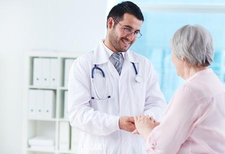 Zekere arts kijken naar zijn hogere patiënt tijdens het spreken aan haar