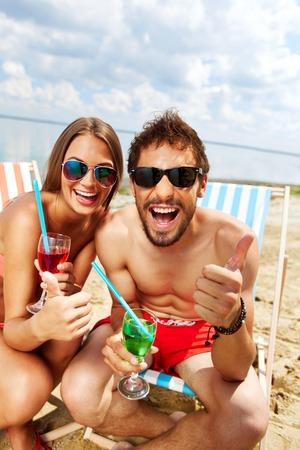 vertical: Pares alegres que se divierten en la fiesta en la playa