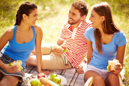 Happy young friends having picnic in the country photo