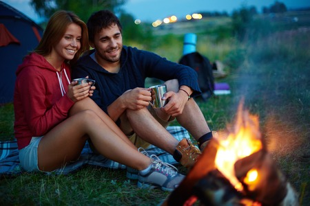 Young couple sitting on the ground and drinking tea while looking at fire in the evening photo