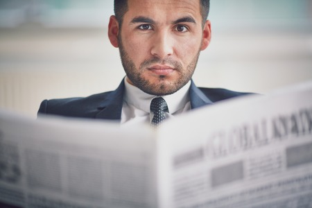 serious businessman: A young serious businessman with newspaper looking at camera