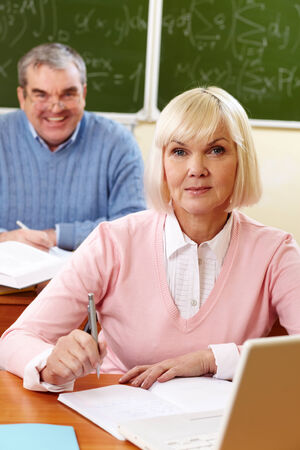 Portrait of blond female looking at camera with senior man on background Stock Photo - 28331872