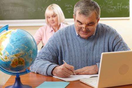 Senior man doing written task in classroom Stock Photo - 28331881