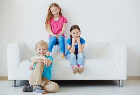 adolescencia: Tres pequeños amigos que miran la cámara con sonrisas