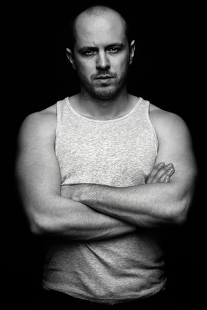Vertical portrait of serious guy with crossed arms looking at camera photo