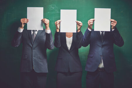 blank papers: Elegant business partners holding blank papers on green background