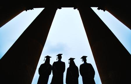 graduacion de universidad: Contornos de cuatro graduados entre columnas de edificio universitario