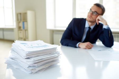 Stack of documents on the desk and pensive male employee working on background photo