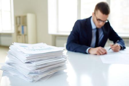 revisando documentos: Pila de documentos en el escritorio y trabajador de sexo masculino que trabajan en el fondo