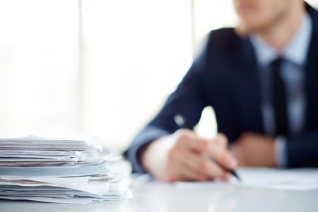 pile of documents: Stack of documents at workplace and male employee on background