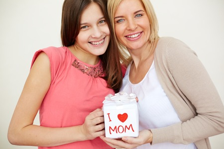 Teenage girl and her mom with giftbox looking at camera and smiling photo