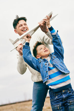 Photo of happy boy and his father playing together outdoors photo