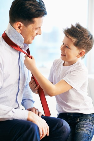 Photo of happy boy tying necktie of his father photo