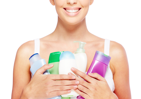 jabon liquido: Primer plano de mujer joven con recipientes con gel de ducha, loción y jabón líquido