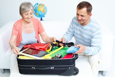 Portrait of happy senior couple packing suitcase