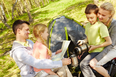 Portrait of family of travelers spending time in forest with tent near by photo