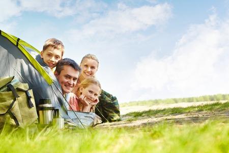 カメラ目線のテントの旅行者の家族の肖像画 写真素材
