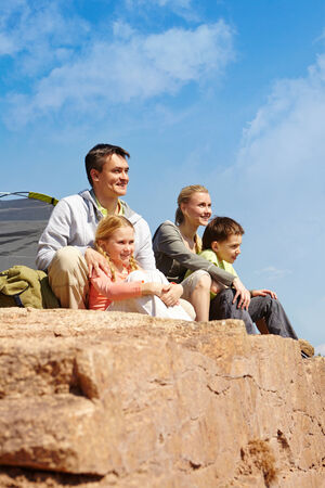 Portrait of family of travelers sitting on rocky cliff photo