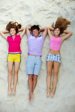 young girl barefoot: Above angle of happy teenage friends lying on sandy beach
