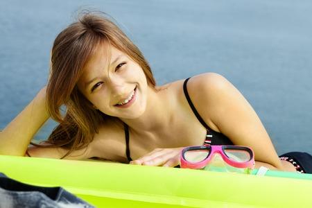 Portrait of teenage girl in bikini lying on mattress and looking at camera photo