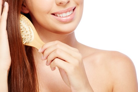hair part: Close-up of young woman brushing her long hair Stock Photo