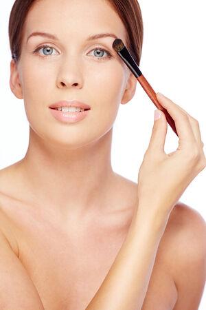 maquillage: Fresh girl applying eyeshadows with brush over white background