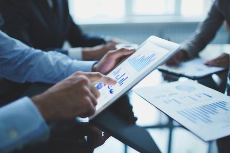 Afbeelding van ondernemer wijzend op document touchpad op de vergadering van Stockfoto
