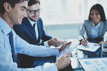 corporate consulting: Image of businessman pointing at document in touchpad while interacting with his partner at meeting Stock Photo