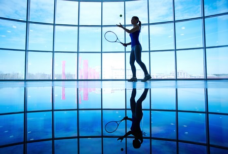 Young female playing tennis in gym on background of window photo