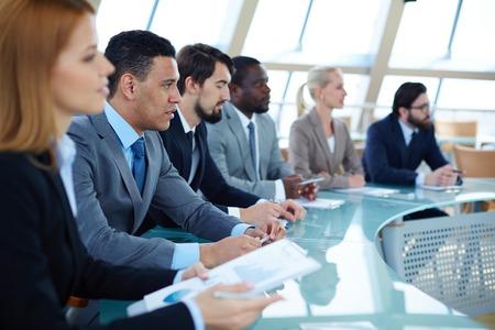 エレガントな若い男に焦点を当てるとセミナーでのプレゼンテーションを聞いているビジネス人々 の行 写真素材