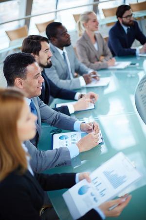 lineas verticales: Fila de gente de negocios de escuchar la presentaci�n en el seminario con enfoque en el hombre joven y elegante