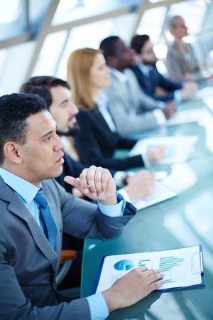 fila de personas: Hombre de negocios joven pensativo escuchando explicaciones en el seminario