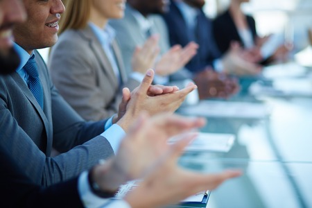 business handshake: Young business partners applauding to reporter after listening to presentation at seminar