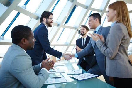 congratulating: Group of business people congratulating their colleagues with striking grand deal Stock Photo