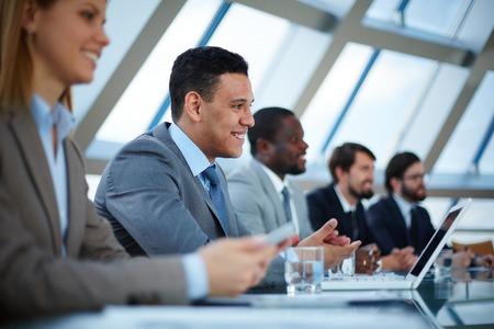 Rij van mensen uit het bedrijfsleven luisteren naar presentatie op seminar met de nadruk op elegante jonge man