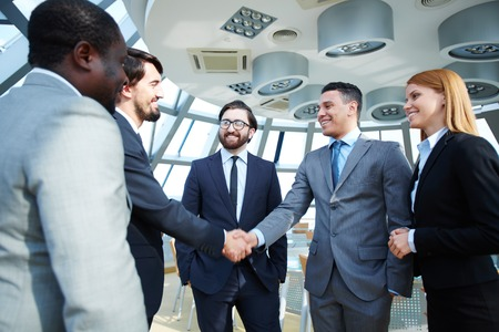 business deal: Group of business people looking at their colleagues handshaking after striking grand deal