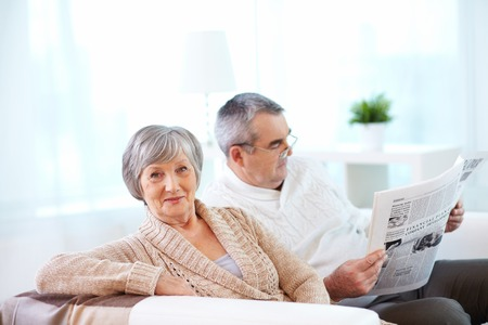 Portrait of mature woman looking at camera on background of her husband reading newspaper Stock Photo