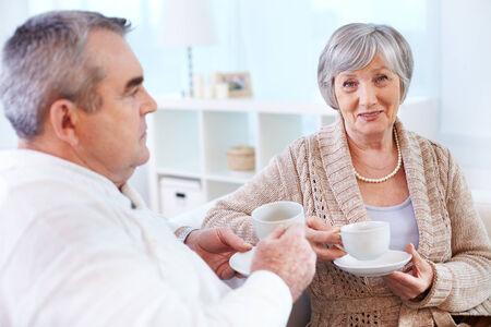 Portrait of mature woman looking at camera while drinking tea and interacting with her husband photo