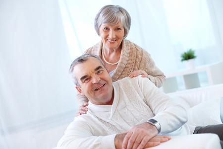 vejez feliz: Retrato de una pareja de ancianos felices mirando a la cámara y sonriendo Foto de archivo