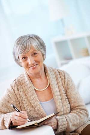 congenial: Portrait of aged female looking at camera while making notes in notebook Stock Photo