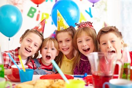 Grupo de niños adorables mirando a la cámara en la fiesta de cumpleaños
