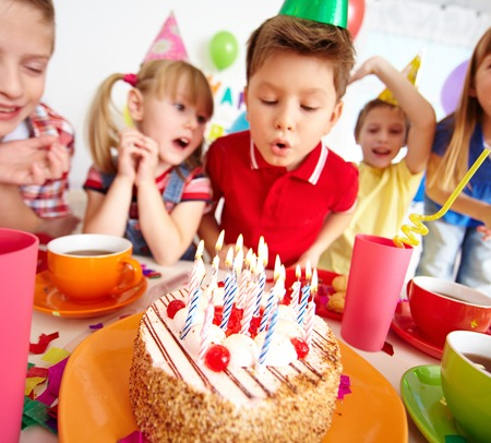 kids birthday party: Group of adorable kids looking at birthday cake with candles, cute boy blowing on them