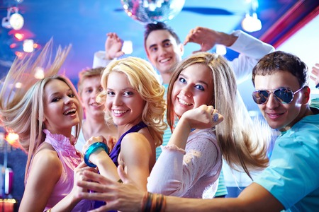 dancing club: Portrait of glamorous girls dancing at party with happy friends near by