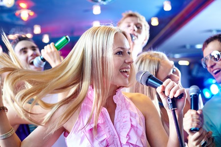Portrait of joyous girl singing at party on background of happy friends photo