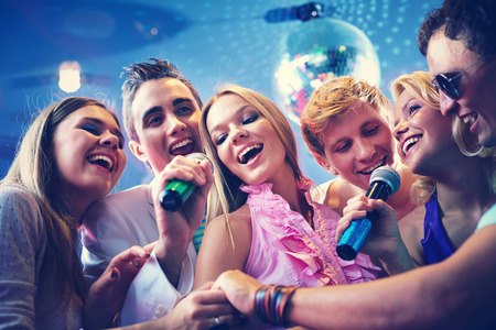 karaoke: Portrait of joyous guys and girls singing at party together