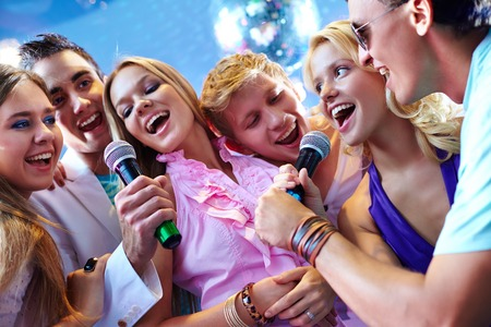 joyous: Portrait of joyous friends singing at party together Stock Photo