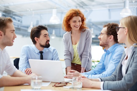 Group of business partners sharing ideas upon computer project at meeting
