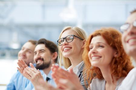 Foto van gelukkige mensen uit het bedrijfsleven applaudisseren op de conferentie, focus op lachende blonde
