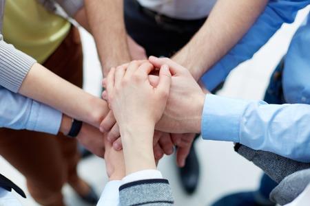 la union hace la fuerza: Socios de negocios de las manos una encima de la otra compa��a que simboliza Foto de archivo